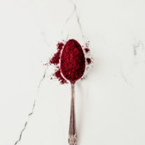 Beetroot powder in a spoon on a white marble countertop